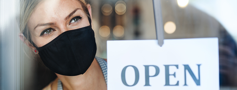 Woman wearing face mask opening a shop